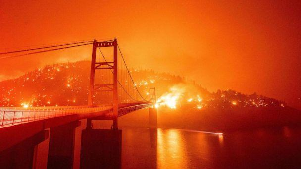 PHOTO: A boat motors by as the Bidwell Bar Bridge is surrounded by fire in Lake Oroville during the Bear fire in Oroville, Calif., on Sept. 9, 2020. (Josh Edelson/AFP via Getty Images)
