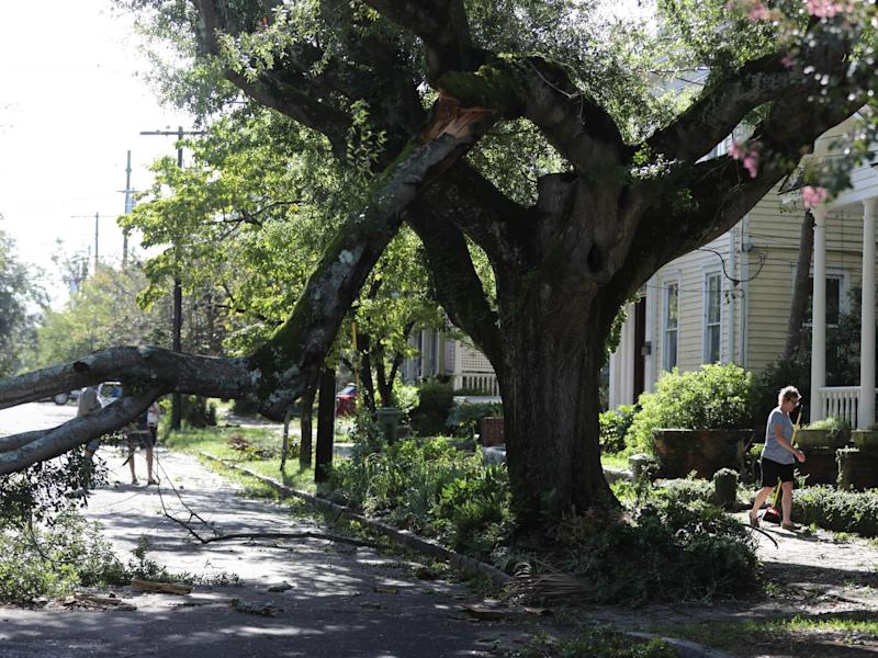 Residents of Wilmington clean up tree branch debris after Hurricane Isaias made landfall near the town the night before in Wilmington, North Carolina on 4 August 2020: (2020 Getty Images)