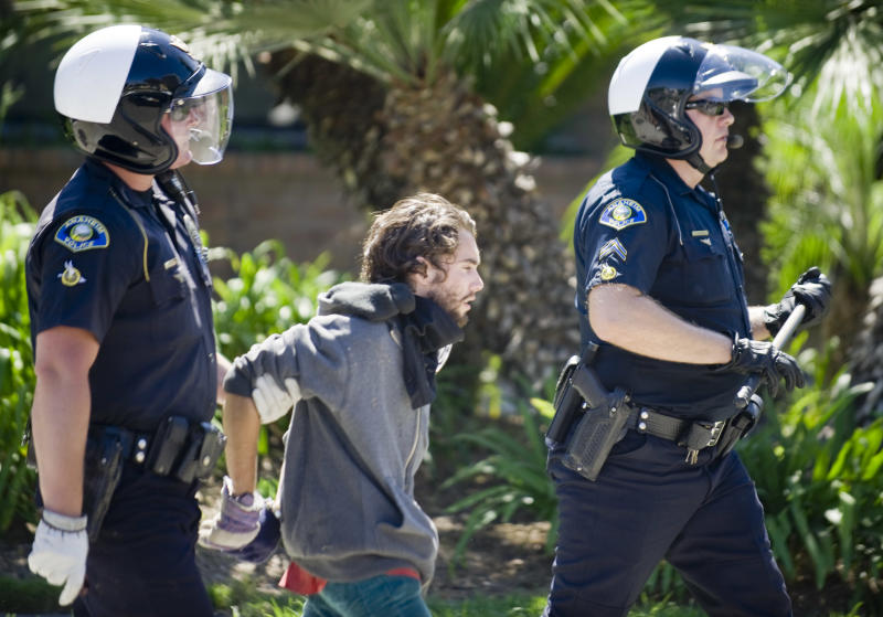 Anaheim police take a man into custody Sunday, July 29, in front of the police department after a day of protests alternating between peaceful and unruly, in Anaheim, Calif. More than 300 demonstrators rallied Sunday to denounce two fatal police shootings and to issue a call for community peace.  (AP Photo/The Orange County Register, Mindy Schauer)   MAGS OUT; LOS ANGELES TIMES OUT