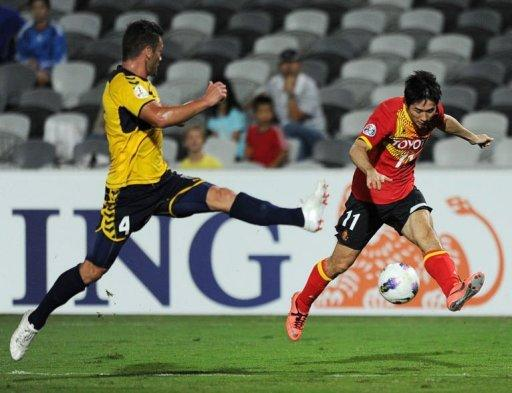 Australia's Central Coast Mariners' Pedj Bojic (L) clashes with Japan's Nagoya Grampus player Tamada Keiji (R)