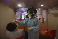 A health worker inside a mobile lab takes nasal swab sample for COVID- 19 testing through rapid antigen methodology in New Delhi, India, Monday, Aug. 10, 2020. India is the third hardest-hit country by the pandemic in the world after the United States and Brazil. (AP Photo/Manish Swarup)