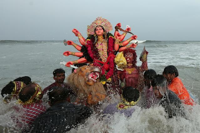 <p>Devotees immerse an idol of the Hindu goddess Durga into the Bay of Bengal on the last day of the Durga Puja festival in Chennai, India, Sept. 30, 2017 . (Photo: P. Ravikumar/Reuters) </p>