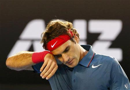 Roger Federer of Switzerland wipes his head during his men's singles semi-final match against Rafael Nadal of Spain at the Australian Open 2014 tennis tournament in Melbourne January 24, 2014. REUTERS/Petar Kujundzic