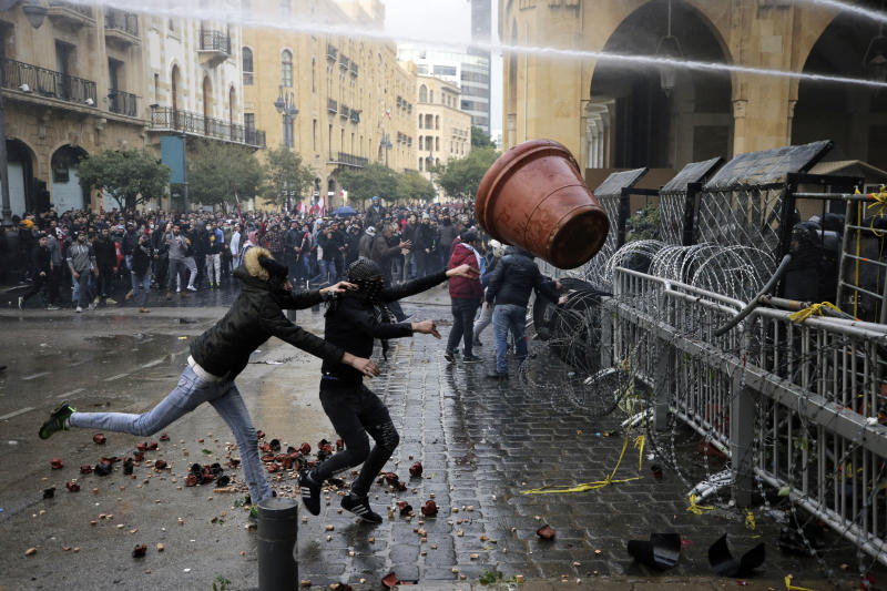 Anti-government demonstrators clash with riot police at a road leading to the parliament building in Beirut, Lebanon, Saturday, Jan. 18, 2020. Riot police fired tears gas and sprayed protesters with water cannons near parliament building to disperse thousands of people after riots broke out during a march against the ruling elite amid a severe economic crisis. (AP Photo/Hassan Ammar)