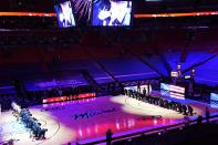 The Boston Celtics and the Miami Heat teams kneel during the playing of the National Anthem before the start of an NBA basketball game, Wednesday, Jan. 6, 2021, in Miami. (AP Photo/Marta Lavandier)