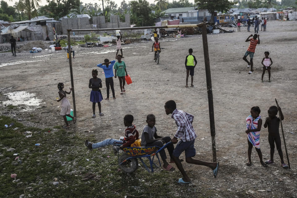 Children play in a field in Les Cayes, Haiti, Friday, Aug. 20, 2021, six days after a 7.2 magnitude earthquake hit the area. (AP Photo/Matias Delacroix)