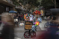 An organ grinder uses a bubble maker as he plays music for tips and sells toys in downtown Santiago, Chile, Friday, May 28, 2021, amid the COVID-19 pandemic. (AP Photo/Esteban Felix)