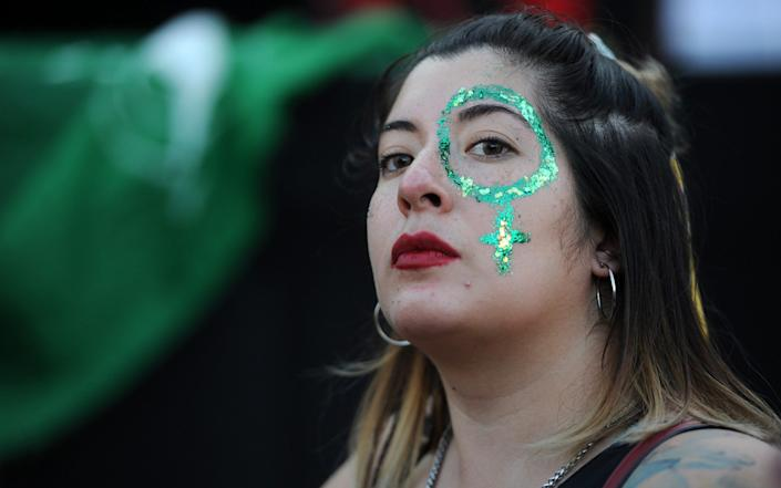 A woman paints her face green during a rally to demand the legalisation of abortion