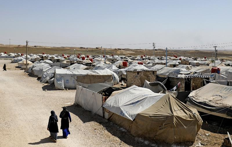 Women stroll in a camp for people who were affilated with the Islamic State group in the northern Syrian village of Malikiya in September 2018