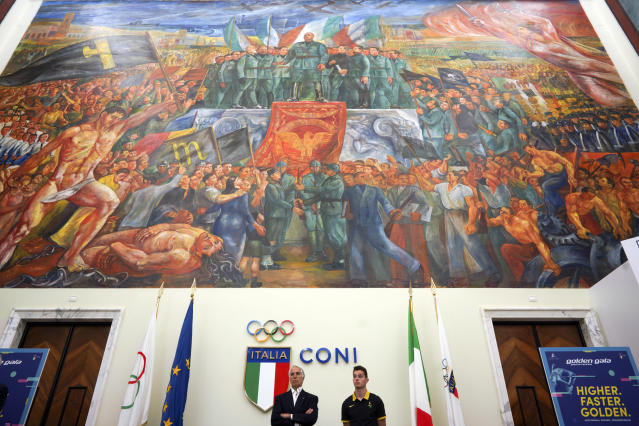 """CONI (Italian Olympic Committee) president Giovanni Malago', bottom left, and Italian athlete Filippo Tortu attend a press conference to present the Golden Gala athletic meeting, as they stand beneath a mural titled """"Apotheosis of Fascism"""", in the Salone d'Onore of the CONI headquarters, in Rome, Tuesday, May 14, 2019. The mural, by Luigi Montanarini, is believed to have been painted between the late 1930's and early 1940's. While Germany systematically wiped out traces of Adolf Hitler's Nazi regime after World War II, the legacy of his Axis ally, Benito Mussolini, remains present in Italy even today. (AP Photo/Andrew Medichini)"""