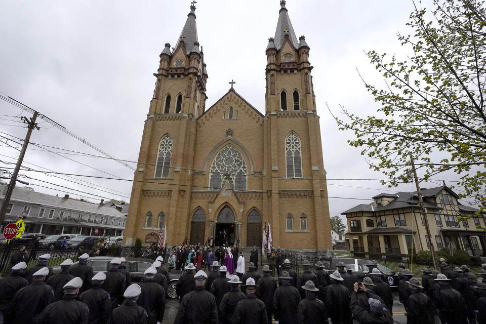 """Members of the Massachusetts state police, below, line the street as mourners for the late U.S. Capitol Police officer William """"Billy"""" Evans, depart St. Stanislaus Kostka Church following a funeral Mass, in Adams, Mass., Thursday, April 15, 2021. Evans, a member of the U.S. Capitol Police, was killed on Friday, April 2, when a driver slammed his car into a checkpoint he was guarding at the Capitol. (AP Photo/Steven Senne)"""