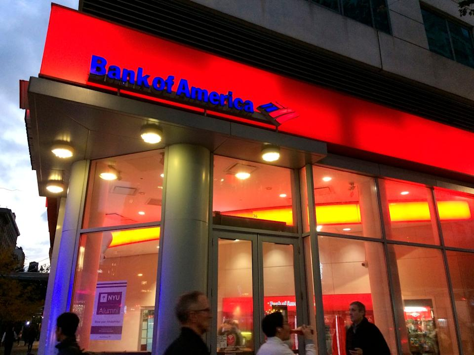 FILE- In this Nov. 6, 2017, file photo, people walk by a branch office of Bank of America in New York. Bank of America Corp. reports earnings Monday, July 16, 2018. (AP Photo/Mark Lennihan, File)