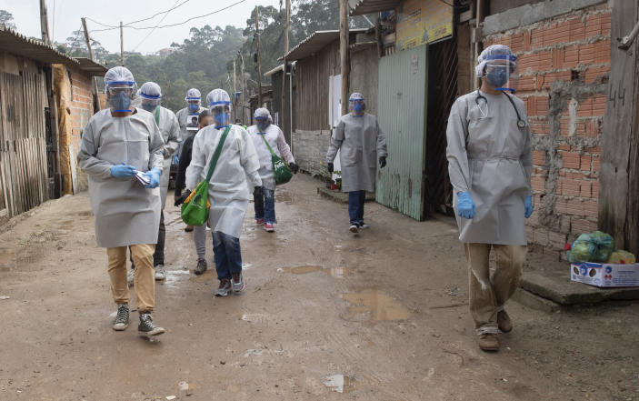Health workers from Doctors Without Borders visit a squatters camp to conduct medical examinations and avoid the spread of the COVID-19 in Sao Bernardo do Campo, greater Sao Paulo area, Brazil, Wednesday, June 3, 2020. (AP Photo/Andre Penner)