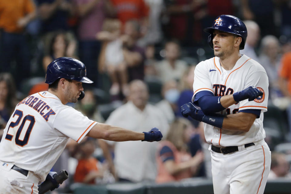 Houston Astros' Chas McCormick (20) reaches to fist-bump Robel Garcia, right, after Garcia's home run during the sixth inning of the team's baseball game against the Minnesota Twins on Thursday, Aug. 5, 2021, in Houston. (AP Photo/Michael Wyke)