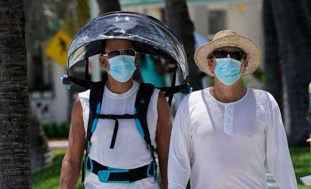PHOTO: A pair of beach goers wear masks to prevent the spread of COVID-19, Aug. 11, 2020, in Miami Beach, Fla. (Wilfredo Lee/AP)