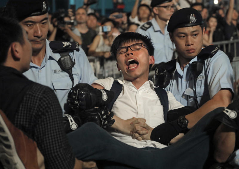 FILE - In this June 28, 2017, file photo, pro-democracy activist Joshua Wong is detained by police officers after he climb up to a giant flower statue bequeathed by Beijing in 1997 in Golden Bauhinia Square of Hong Kong. Overseas, Joshua Wong has emerged as a prominent face of Hong Kong's months-long protests for full democracy. At home, he is just another protester. (AP Photo/Vincent Yu, File)