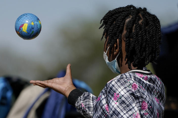 A Haitian migrant girl plays with a ball in the shape of a globe while waiting to board a bus to Houston provided by a humanitarian group after she and her family were released from U.S. Customs and Border Protection custody, Friday, Sept. 24, 2021, in Del Rio, Texas. (AP Photo/Julio Cortez)