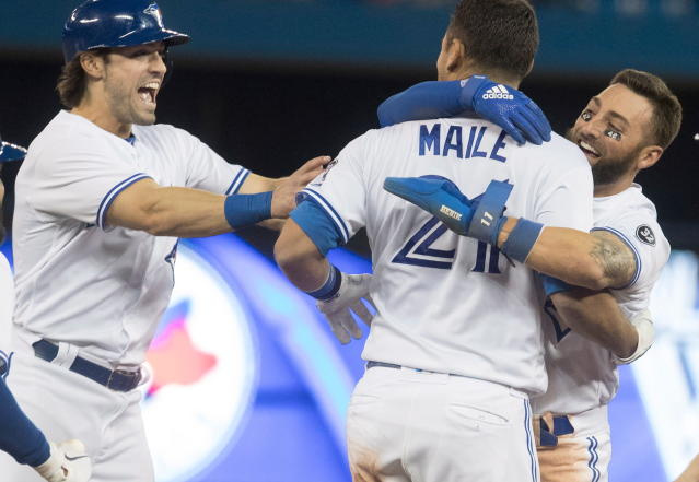 Toronto Blue Jays catcher Luke Maile is embraced by teammate Kevin Pillar after he hit a single in the tenth inning to drive Pillar home and defeat the Kansas City Royals in the second game of their baseball double header, in Toronto on Tuesday, April 17, 2018. (Fred Thornhill/The Canadian Press via AP)