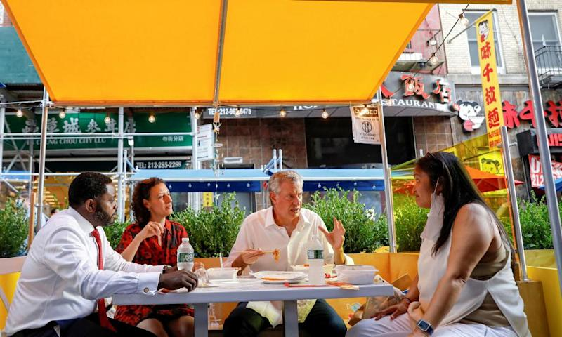 New York City Mayor Bill de Blasio eats lunch with staff members outside the Wo Hop restaurant in Chinatown.