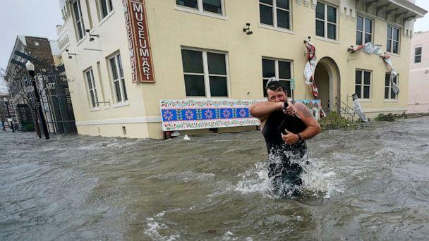 PHOTO: Trent Airhart wades through flood waters, Sept. 16, 2020, in downtown Pensacola, Fla. (Gerald Herbert/AP)