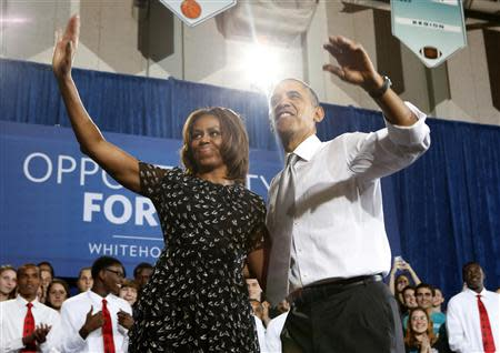 U.S. President Barack Obama and first lady Michelle Obama wave to the audience at the Coral Reef High School in Miami, Florida, March 7, 2014. REUTERS/Yuri Gripas