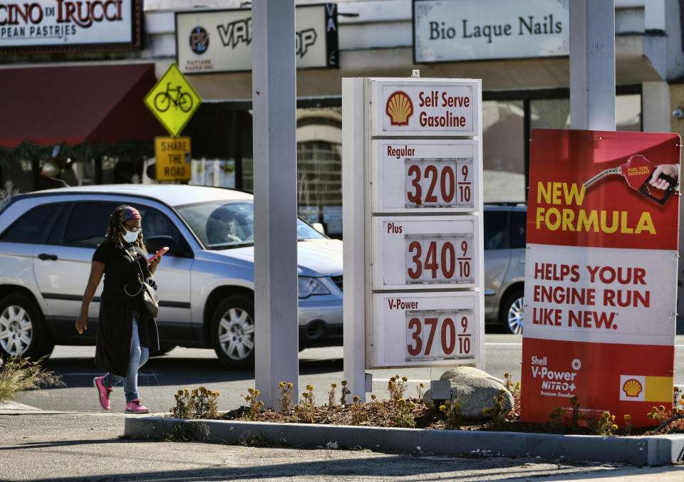 A masked pedestrian walks past a self-service gas station in the Sherman Oaks section of Los Angeles, Sunday, Dec. 6, 2020. (AP Photo/Richard Vogel)