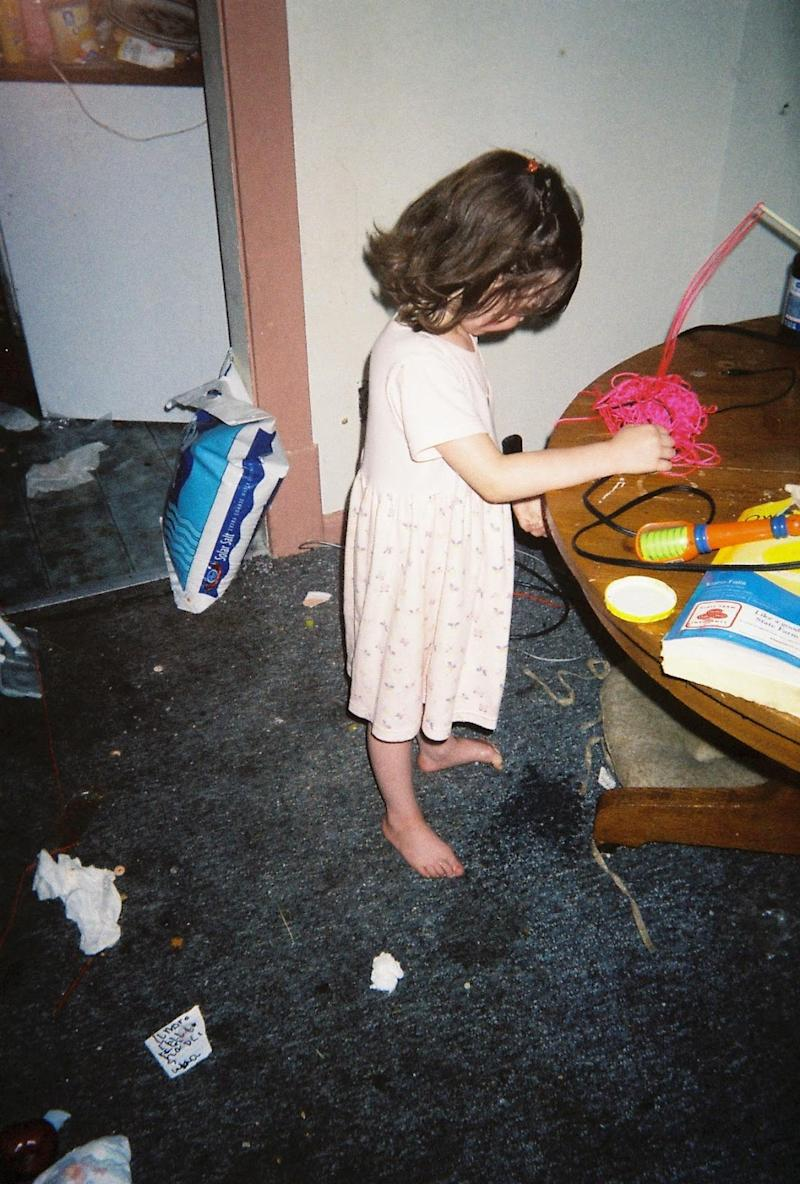 Brynlee's older sister stands barefoot on the dirty carpet inside their childhood home surrounded by filth.