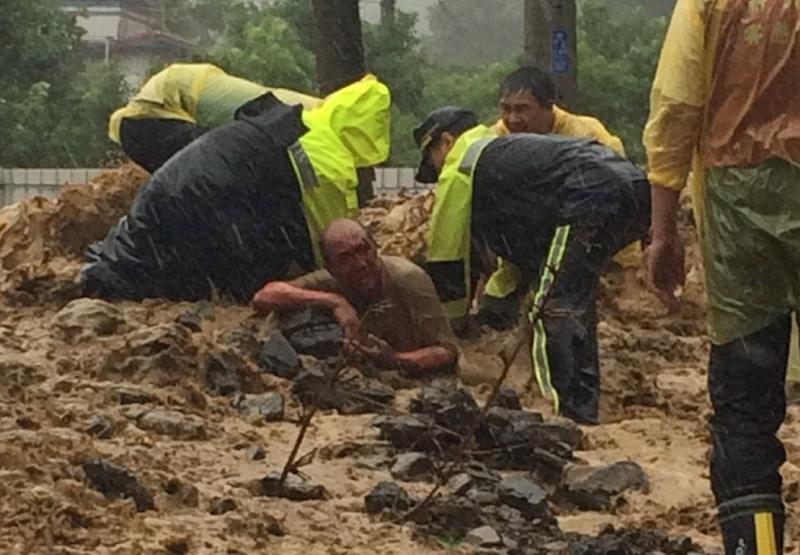 Rescue personnel extricate a man from mud and rubble in Wulai, New Taipei City, on August 8, 2015 as Typhoon Soudelor hits Taiwan (AFP Photo/)