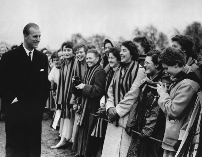 FILE - In this March 10, 1957 file photo, Britain's Prince Philip is greeted by some of the students of St. Mary's College, in Cheltenham, England, as he left the playing fields of St. Paul's College. Buckingham Palace officials say Prince Philip, the husband of Queen Elizabeth II, has died, it was announced on Friday, April 9, 2021. He was 99. Philip spent a month in hospital earlier this year before being released on March 16 to return to Windsor Castle. Philip, also known as the Duke of Edinburgh, married Elizabeth in 1947 and was the longest-serving consort in British history. (AP Photo/File)