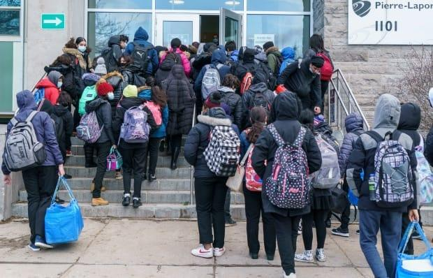 Students enter the Pierre Laporte Secondary School in Montreal Monday as all high school grades return to classes full time. Montreal is unaffected by the new lockdown, but in  Quebec City, Lévis and Gatineau schools will move to full-time remote learning.
