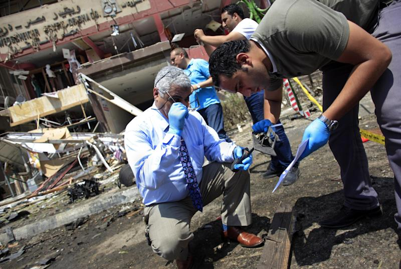 "Egyptian security officers gather evidence at the scene of a bomb attack targeting the convoy of Egypt's Interior Minister Mohammed Ibrahim, in Nasr City, Cairo, Egypt, Thursday, Sept. 5, 2013. A ""large"" explosive targeted the convoy of Egypt's interior minister Thursday, the first attack on a senior government official since a coup toppled the country's Islamist president July 3, 2013. (AP Photo/Khalil Hamra)"