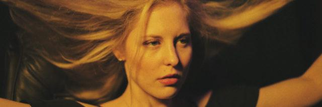 A blond woman wearing black, lifting her hair up