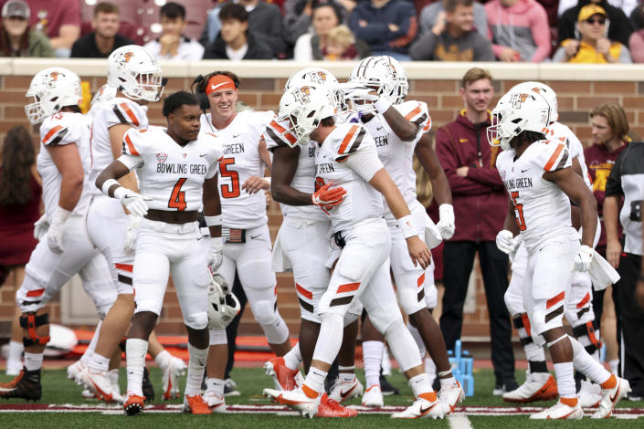 Bowling Green quarterback Matt McDonald (3) celebrates with teammates on the sideline after scoring a touchdown against Minnesota during the first half of an NCAA college football game Saturday, Sept. 25, 2021, in Minneapolis. (AP Photo/Stacy Bengs)