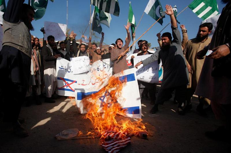 Supporters of the Difa-e-Pakistan Council (DPC), an Islamic organization, chant slogans as they burn Israeli and US flags in Pakistan. (REUTERS)