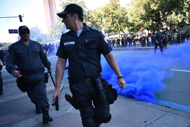 Police walk past a smoke bomb during a protest against the FIFA World Cup to demand better social services near the Maracana Stadium in Rio de Janeiro on July 13, 2014 (AFP Photo/Yasuyoshi Chiba)