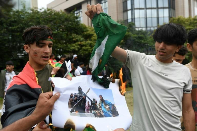 Afghan demonstrators in Brussels burn a flag of Pakistan as they protest the Taliban takeover of Afghanistan