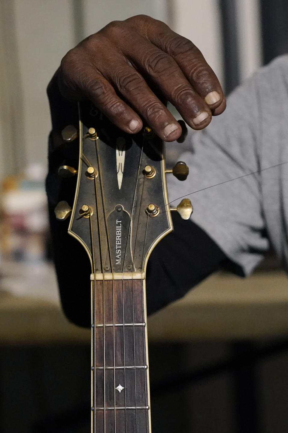 "Resting his hand against the head of his acoustic guitar, blues performer Jimmy ""Duck"" Holmes' fingertips show the wear after years of performing without a pic at the Blue Front Cafe in Bentonia, Miss., Jan. 21, 2021. Holmes' ninth album, ""Cypress Grove,"" has earned a Grammy nomination for the Best Traditional Blues Album. (AP Photo/Rogelio V. Solis)"