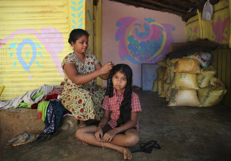 """In this March 28, 2019, photo, Sangeetha Nandini, 29, from the Warli tribe, combs the hair of her cousin at Sanjay Gandhi National Park in Mumbai. """"They want to move us out of the forest and into buildings. Our forefathers have lived here and died here, so we want the same right. Moving us into buildings means keeping us in cages,"""" she said. The biggest worry for many tribals is losing their land, which has grown increasingly valuable in recent years as India's economy has boomed. Many Warlis, for instance, are facing threat of relocation by the government to housing projects. (AP Photo/Rafiq Maqbool)"""