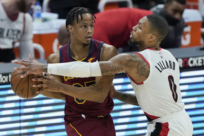 Portland Trail Blazers' Damian Lillard (0) defends against Cleveland Cavaliers' Isaac Okoro during the second half of an NBA basketball game Wednesday, May 5, 2021, in Cleveland. (AP Photo/Tony Dejak)
