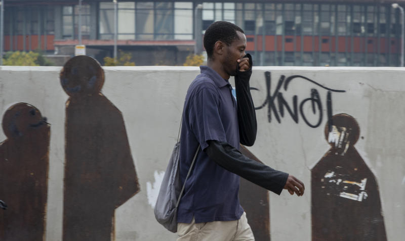 A man uses his hand to cover his nose as he walks along a downtown street Johannesburg, South Africa, Monday, March 16, 2020. South African President Cyril Ramaphosa declared a national state of disaster. Ramaphosa said all schools will be closed for 30 days from Wednesday and he banned all public gatherings of more than 100 people. South Africa will close 35 of its 53 land borders and will intensify screening at its international airports. For most people, the new COVID-19 coronavirus causes only mild or moderate symptoms. For some it can cause more severe illness. (AP Photo/Themba Hadebe)