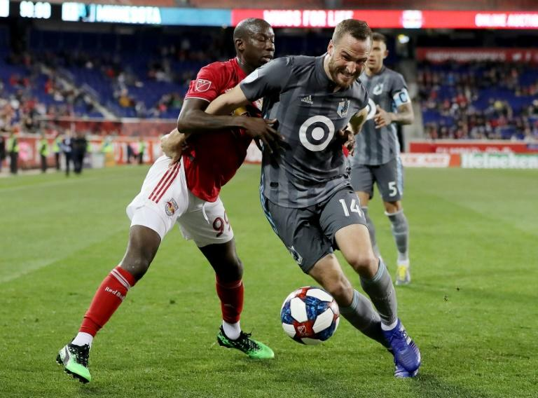 Minnesota United's Brent Kallman (R) battles for the ball with Bradley Wright-Phillips