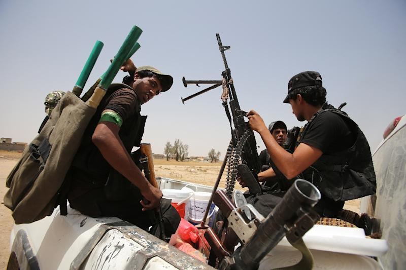 Iraqi Shiite fighters from the Popular Mobilisation units ride on the back of a vehicle in the city of Baiji, north of Tikrit, as they fight alongside Iraqi forces against the Islamic State (IS) jihadist group, on June 9, 2015 (AFP Photo/Ahmad al-Rubaye)