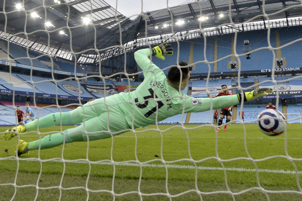 Manchester United's Bruno Fernandes, center right, scores the opening goal from the penalty spot past Manchester City's goalkeeper Ederson during the English Premier League soccer match between Manchester City and Manchester United at the Etihad Stadium in Manchester, England, Sunday, March 7, 2021. (Peter Powell/Pool via AP)