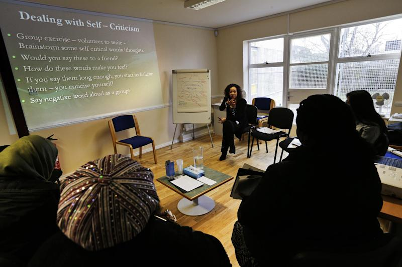In this Feb. 5, 2013 photo, psychological well-being practitioner Nabila El-Zanaty, center, talks to a self-help psychological course class run by Britain's publicly funded health system, during a session in east London. With a long wait to see a psychologist, the British government is turning to the classroom to treat people with mild to moderate mental health problems with a mix of PowerPoint presentations and group exercises. While some dismiss the approach as do-it-yourself therapy, experts say there is convincing evidence that people with conditions like depression and anxiety can be successfully treated without ever seeing a psychologist or a psychiatrist. (AP Photo/Lefteris Pitarakis)