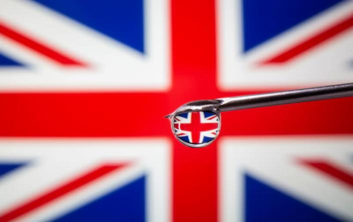 A British flag is reflected in a drop on a syringe needle in this illustration
