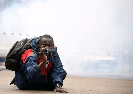 A Ugandan journalist uses his camera after riot policemen fired tear gas to disperse activists led by musician turned politician, Robert Kyagulanyi, during a demonstrating against new taxes including a levy on access to social media platforms in Kampala, Uganda July 11, 2018. REUTERS/Newton Nambwaya