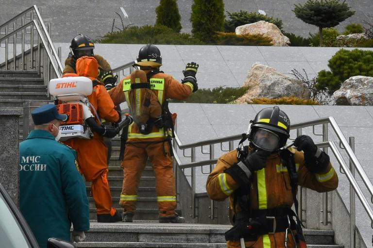 Emergency personnel wearing protective gear spray disinfectant on colleagues at the site of a fire linked to ventilators at the Saint George hospital in Saint Petersburg on May 12, 2020