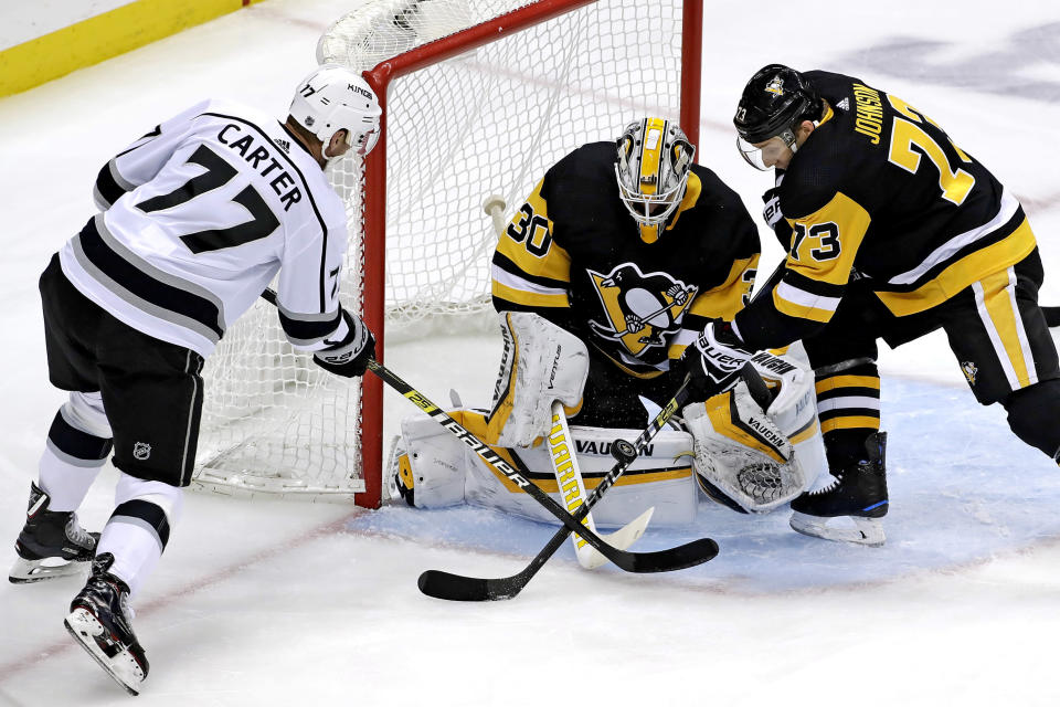 FILE - Los Angeles Kings' Jeff Carter (77) can't get his stick on a rebound in front of Pittsburgh Penguins goaltender Matt Murray (30) with Jack Johnson (73) defending during the first period of an NHL hockey game in Pittsburgh, in this Saturday, Dec. 15, 2018, file photo. All divisional play during this shortened NHL season gives an added perk to most of the players traded at the deadline: They'll get to face different teams. Jeff Carter is plenty used to Eastern opponents after starting with the Flyers but will be glad to play in front of some home fans with the Penguins. (AP Photo/Gene J. Puskar, File)