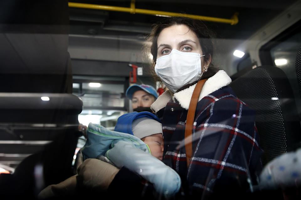 MOSCOW REGION, RUSSIA - APRIL 15, 2020: A Russian traveller with a child boards a minibus at Terminal F at the Sheremetyevo International Airport after arriving on an Aeroflot charter flight from New York City, United States, during the pandemic of the novel corinavirus disease (COVID-19). Since 27 March 2020, Russia suspended all international flights with the exception of evacuation flights, to counter the spread of coronavirus. Artyom Geodakyan/TASS EDITORIAL USE ONLY; NO COMMERCIAL USE; NO ADVERTISING (Photo by Artyom Geodakyan\TASS via Getty Images)