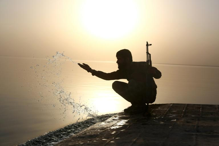 A member of the US-backed Syrian Democratic Forces splashes water at Lake Assad on April 29, 2017